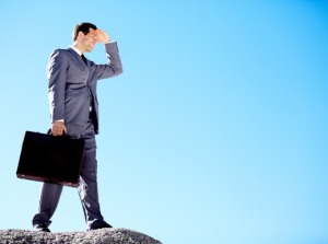 A well dressed business man holds a briefcase while shielding his eyes from the sun and standing on a rocky hilltop